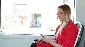 Νέο ξανθό οδηγώντας τραμ γυναικών, που δακτυλογραφεί σε κινητό, τηλέφωνο, κύτταρο, γυαλιά μακριά φιλμ μικρού μήκους