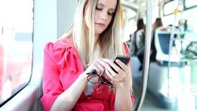 Νέο ξανθό οδηγώντας τραμ γυναικών, που δακτυλογραφεί σε κινητό, τηλέφωνο, κύτταρο, που κρατά τα γυαλιά φιλμ μικρού μήκους