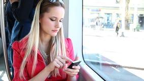 Νέο ξανθό οδηγώντας τραμ γυναικών, που δακτυλογραφεί σε κινητό, τηλέφωνο, κύτταρο φιλμ μικρού μήκους