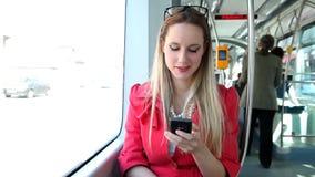 Νέο ξανθό οδηγώντας τραμ γυναικών, που δακτυλογραφεί σε κινητό, τηλέφωνο, κύτταρο, χαμόγελο απόθεμα βίντεο