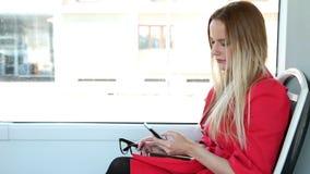Νέο ξανθό οδηγώντας τραμ γυναικών, που δακτυλογραφεί σε κινητό, τηλέφωνο, κύτταρο, που κρατά τα γυαλιά απόθεμα βίντεο