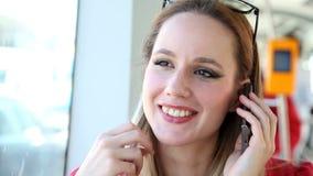 Νέο ξανθό οδηγώντας τραμ γυναικών, που μιλά σε κινητό, τηλέφωνο, κύτταρο, που παίζει με την τρίχα της απόθεμα βίντεο