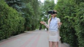 Νέο ξανθό παίζοντας παιχνίδι γυναικών που χρησιμοποιεί το VR-κράνος για τα έξυπνα τηλέφωνα απόθεμα βίντεο