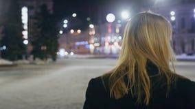 Νέο ξανθό περπάτημα σε μια οδό νύχτας που απολαμβάνει μια ζωή Πόλη νύχτας με τα φω'τα bokeh φιλμ μικρού μήκους
