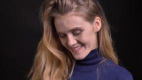 Νέο ξανθό πρότυπο στην μπλε προσοχή πουλόβερ στη κάμερα με το φλερτάροντας και μυστήριο χαμόγελο στο μαύρο υπόβαθρο φιλμ μικρού μήκους