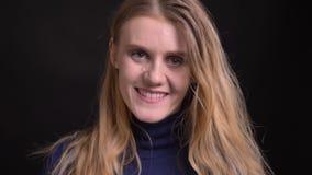 Νέο ξανθό πρότυπο στο μπλε πουλόβερ που φλερτάρει με τη κάμερα σχετικά με το πρόσωπό της tenderly στο μαύρο υπόβαθρο φιλμ μικρού μήκους
