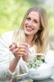 Νέο ξανθό τσάι κατανάλωσης κοριτσιών Στοκ Φωτογραφία
