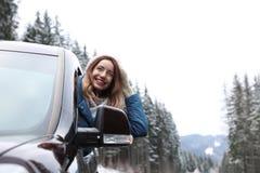 Νέο οδηγώντας αυτοκίνητο γυναικών και κοίταγμα από το παράθυρο στο δρόμο στοκ εικόνες