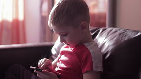 Νέο παίζοντας παιχνίδι αγοριών στο smartphone στο σπίτι απόθεμα βίντεο