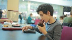 Νέο παίζοντας παιχνίδι εφήβων στο smartphone στον καφέ απόθεμα βίντεο