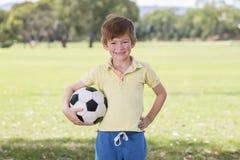 Νέο παιδάκι 7 ή 8 χρονών που απολαμβάνει το ευτυχές παίζοντας ποδόσφαιρο ποδοσφαίρου στον τομέα πάρκων πόλεων χλόης που θέτει την στοκ φωτογραφία