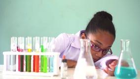 Νέο παιδί αφροαμερικάνων που χρησιμοποιεί το μικροσκόπιο στο εργαστήριο φιλμ μικρού μήκους