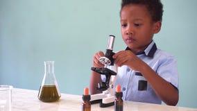 Νέο παιδί αφροαμερικάνων που χρησιμοποιεί το μικροσκόπιο στο εργαστήριο απόθεμα βίντεο