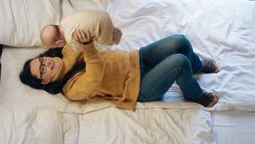 Νέο παιχνίδι γυναικών με το μωρό στο κρεβάτι Ευτυχής μητέρα που κρατά το νεογέννητο παιδί της απόθεμα βίντεο