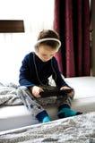 Νέο παιχνίδι αγοριών στο κινητό τηλέφωνό του στο κρεβάτι Στοκ Φωτογραφίες