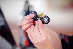 Νέο παιχνίδι γυναικών με ένα δημοφιλές fidget παιχνίδι κλωστών στα χέρια της, στο υπόβαθρο γραφείων Στοκ φωτογραφία με δικαίωμα ελεύθερης χρήσης