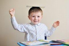 Νέο παιχνίδι μαθητών με τα βιβλία και χαμόγελο όπως κάθεται στο γραφείο του στην τάξη Στοκ φωτογραφίες με δικαίωμα ελεύθερης χρήσης