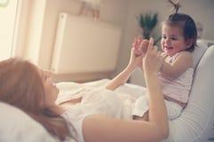 Νέο παιχνίδι μητέρων με το κοριτσάκι της στο κρεβάτι Απόλαυση μητέρων Στοκ Εικόνες