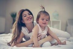 Νέο παιχνίδι μητέρων με το κοριτσάκι της στο κρεβάτι Απόλαυση μητέρων Στοκ φωτογραφίες με δικαίωμα ελεύθερης χρήσης