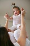 Νέο παιχνίδι μητέρων με το κοριτσάκι της στο κρεβάτι Απόλαυση μητέρων Στοκ εικόνα με δικαίωμα ελεύθερης χρήσης