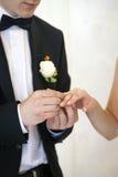 Νέο παντρεμένο ζευγάρι, που ανταλλάσσει τα γαμήλια δαχτυλίδια Στοκ φωτογραφία με δικαίωμα ελεύθερης χρήσης
