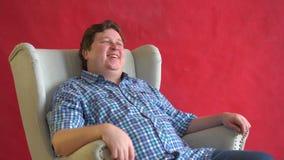 Νέο παχύ άτομο, πουκάμισο καρό, που κάθεται στην καρέκλα και δυνατά που γελά που απομονώνεται στο κόκκινο υπόβαθρο - έννοια διασκ απόθεμα βίντεο