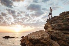 Νέο περιστασιακό άτομο που στέκεται στο βράχο βουνών Στοκ Φωτογραφίες