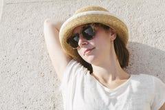 Νέο περιστασιακό κορίτσι ένα καπέλο και τα γυαλιά ηλίου που χαλαρώνουν που φορά Στοκ φωτογραφία με δικαίωμα ελεύθερης χρήσης