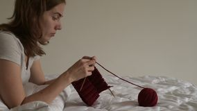 Νέο πλέξιμο γυναικών σε ένα κρεβάτι φιλμ μικρού μήκους