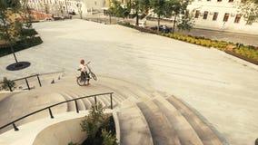 Νέο ποδήλατο γυναικών που περπατά κάτω από τα σκαλοπάτια και που κρατά το ποδήλατο χεριών του φιλμ μικρού μήκους