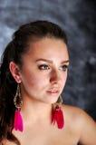 Νέο πορτρέτο γυναικών με τα μακριά κόκκινα σκουλαρίκια στοκ εικόνες