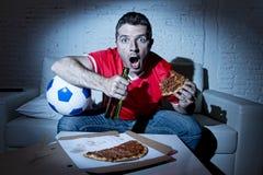 Νέο ποδοσφαιρικό παιχνίδι προσοχής ατόμων ανεμιστήρων στη TV στο βάσανο του Τζέρσεϋ ομάδων νευρικό και την πίεση Στοκ Εικόνες