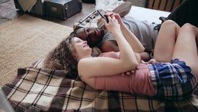 Νέο πολυφυλετικό ζεύγος στις πυτζάμες που βρίσκονται στο κρεβάτι και που φαίνονται φωτογραφίες Smartphone χρήσης ανδρών και γυναι Στοκ Εικόνες