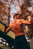 Νέο προκλητικό άτομο αθλητών με το γυμνό κορμό που κάνει το τράβηγμα-UPS στο πάρκο στοκ εικόνες με δικαίωμα ελεύθερης χρήσης