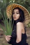 Νέο προκλητικό βιετναμέζικο κορίτσι σε ένα καπέλο αχύρου σε ένα τροπικό δάσος στοκ εικόνες