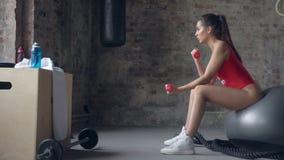 Νέο προκλητικό κορίτσι στη σφαίρα ικανότητας που κάνει τις ασκήσεις με τους αλτήρες, τον αθλητισμό και την υγιή έννοια τρόπου ζωή φιλμ μικρού μήκους