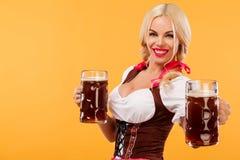 Νέο προκλητικό κορίτσι Oktoberfest - σερβιτόρα, που φορά ένα παραδοσιακό βαυαρικό φόρεμα, που εξυπηρετεί μεγάλες τις κούπες μπύρα Στοκ εικόνες με δικαίωμα ελεύθερης χρήσης