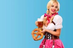Νέο προκλητικό κορίτσι Oktoberfest - σερβιτόρα, που φορά ένα παραδοσιακό βαυαρικό φόρεμα, που εξυπηρετεί μεγάλες τις κούπες μπύρα Στοκ Εικόνες