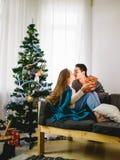 Νέο προκλητικό φίλημα ζευγών μπροστά από το χριστουγεννιάτικο δέντρο, ανοίγοντας παρόν γυναικών στοκ φωτογραφίες