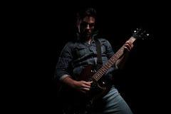 Νέο προκλητικό άτομο που παίζει μια ηλεκτρική κιθάρα με το πάθος στοκ εικόνες