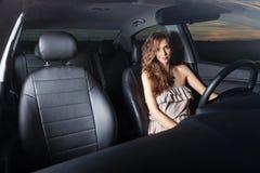 Νέο προκλητικό κορίτσι πίσω από τη ρόδα του αυτοκινήτου που χαμογελά στη κάμερα υπαίθρια Στοκ Εικόνα