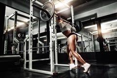 Νέο προκλητικό κορίτσι brunette στη γυμναστική που κάνει τη στάση οκλαδόν με το barbell Στοκ φωτογραφία με δικαίωμα ελεύθερης χρήσης