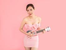 Νέο προκλητικό παιχνίδι γυναικών στη μικρή κιθάρα Πορτρέτο στο ρόδινο backg στοκ εικόνα