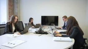 Νέο προσωπικό που εργάζεται με τα lap-top και που μιλά στο σύγχρονο γραφείο Άνδρας στα γυαλιά και τρεις γυναίκες φιλμ μικρού μήκους