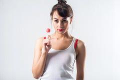 Νέο πρότυπο brunette με το lollipop που θέτει το στούντιο που πυροβολείται υπόβαθρο, που δεν απομονώνεται στο άσπρο στοκ εικόνες