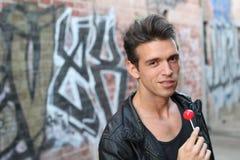 Νέο πρότυπο brunette με το lollipop στο αστικό υπόβαθρο που απομονώνεται Στοκ εικόνες με δικαίωμα ελεύθερης χρήσης