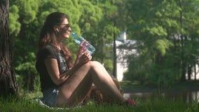 Νέο πόσιμο νερό γυναικών από το μπουκάλι στο πάρκο απόθεμα βίντεο