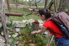 Νέο πόσιμο νερό ταξιδιωτικών κοριτσιών από το ρεύμα βουνών με τα χέρια της Στοκ Εικόνες