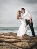 Νέο ρομαντικό ζεύγος που χορεύει στους βράχους παραλιών με τη σαμπάνια Στοκ εικόνες με δικαίωμα ελεύθερης χρήσης