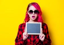 Νέο ρόδινο κορίτσι τρίχας στο κόκκινο πουκάμισο ταρτάν και πίνακας Στοκ Εικόνες